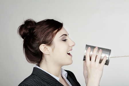 woman in a smart busnisess suit in communication using a tin can and string