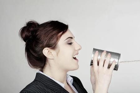 vrouw in een slimme busnisess pak in de communicatie met behulp van een blikje en string