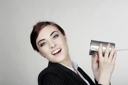 woman in a smart busnisess suit in communication using a tin can and string photo