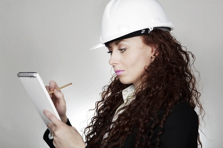 woman wearing a white hard hat making notes photo