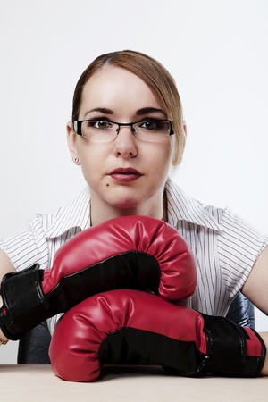 woman at her desk wearing boxing gloves trying to work photo