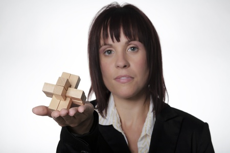 solves: woman in business suit holding up a wooden 3D puzzle  Stock Photo