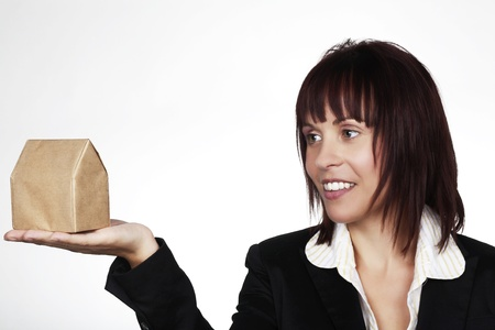 hold up: woman hold up a small model house wrapped up