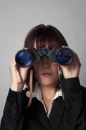 woman in a suit holding up binocular to her eyes Stock Photo - 11954726