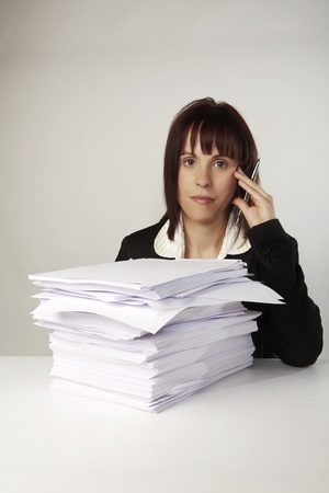 woman at a desk with a lot of paper work to get through photo