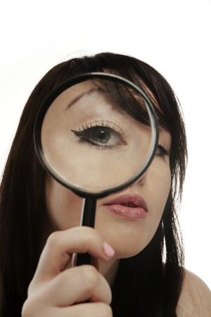 woman holding a magnifying glass up to her eye so it looks really big photo
