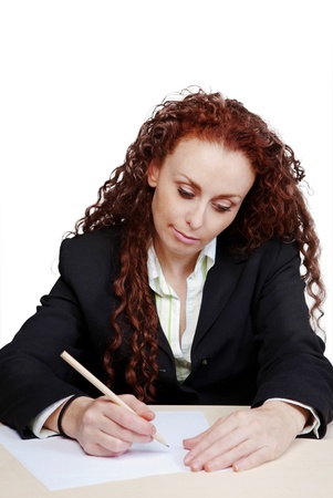 woman at her desk writing on paper photo