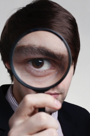 hold up: man hold up a magnifying glass to his eye so his eye looks very large