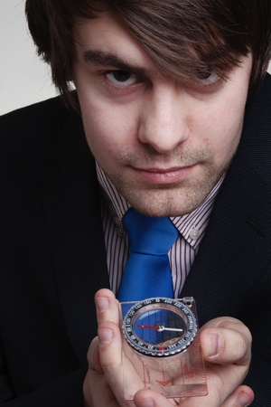 businessman holding up to his face a compass so he can see where he is going photo