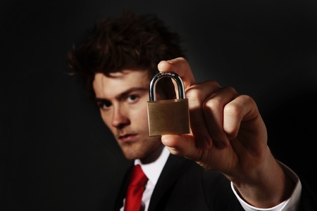 mn: low key portrait image of businessman holding up a pad lock