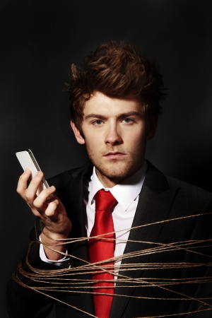 low key image of businessman on a mobile phone all tied up photo
