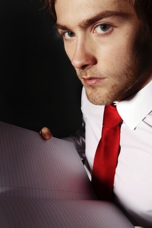 close up low key image of a young man holding a note book Stock Photo - 12503262