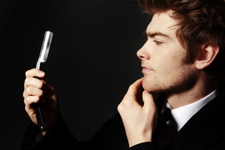 straight man: low key image of a young man holding a cut throat razor what could his intentions be Stock Photo
