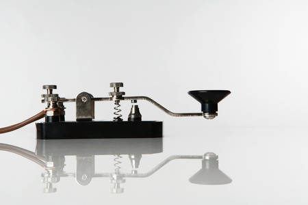 still life image of a morse code key on a white background