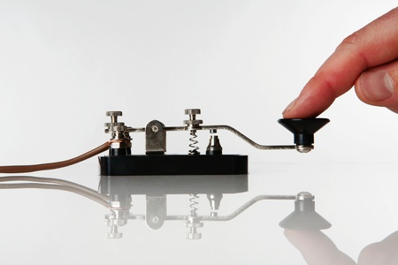 morse code key on a white background with someone sending a message Stock Photo
