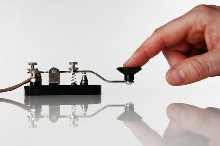 telegraaf: morse code sleutel op een witte achtergrond met iemand een bericht te sturen