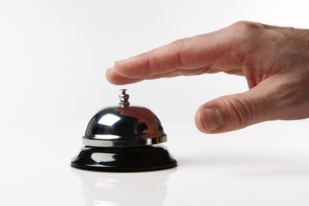 someones hand pressing a service bell what could they want photo