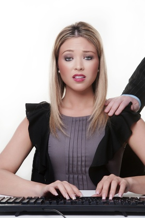 shoulder: woman at her desk with a mans hand on her shoulder she not looking to happy is this sexual harassment Stock Photo