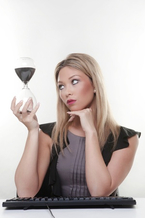 woman holding a large glass sand timer in her hands watching time run out photo