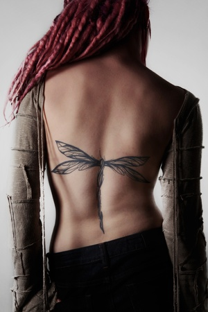 dreadlock: woman with dread lock hair showing off her large back tattoo of a dragonfly