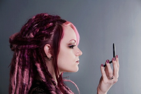 dread: woman with dread lock hair doing her make up Stock Photo