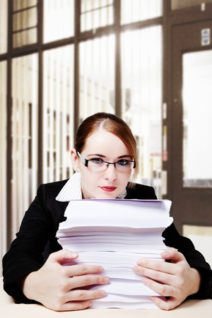 woman at her desk looking at all the paper work she has to do photo
