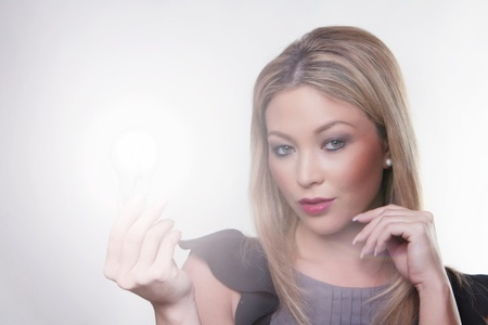 beautiful woman holding up a light bulbs in her hand with the bulb alight Stock Photo - 13330871