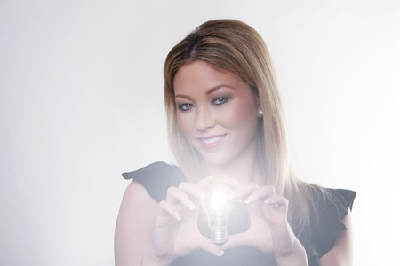 beautiful woman holding up a light bulbs in her hand with the bulb alight photo