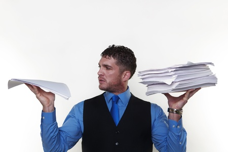 man holding a lot of paper work up in the air a pile in each hand photo