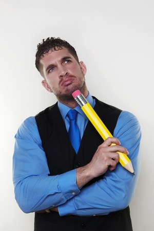 business man with a very large pencil looking a bit silly Stock Photo - 13735504