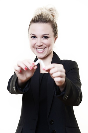 quit: businesswoman holding out and breaking a cigarette in half symbolizing shes giving up smoking Stock Photo
