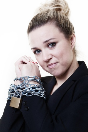 locked up: businesswoman with her wrists in chains and locked up