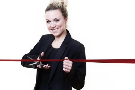 taglio del nastro: donna in piedi il taglio del nastro con un paio di forbici Archivio Fotografico