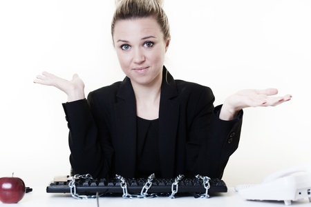 locked up: woman at her desk at a loss of what to do when she has found her computer all locked up with chain and a pad lock