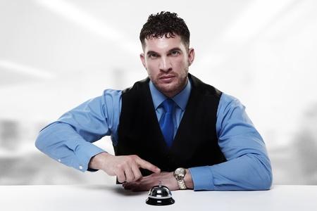 hombre de negocios sentado en un escritorio con un timbre para llamar frente a él