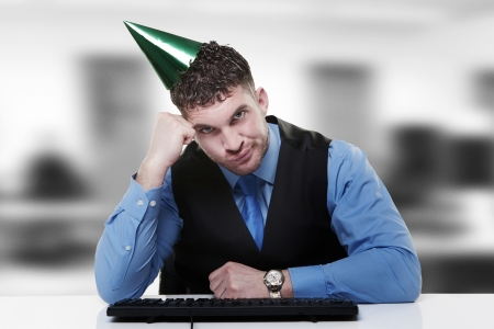 businessman wearing a party hat sitting at his desk photo