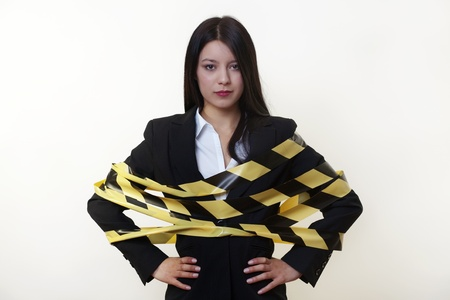 business woman with hazard tape wrapped around her Stock Photo - 14240479