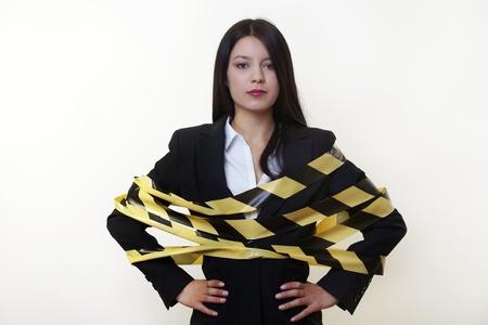 hazard tape: business woman with hazard tape wrapped around her Stock Photo