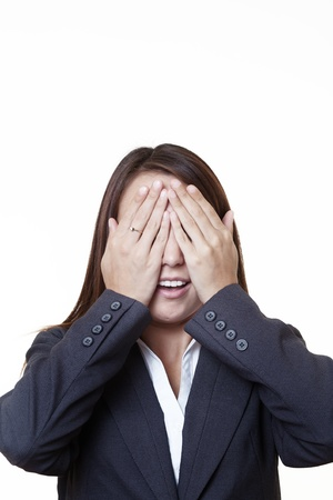 young looking woman in a suit covering her eyes with her hands photo