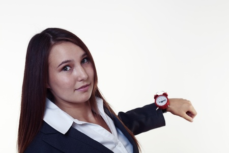 very young looking woman in a suit holding up her watch photo
