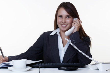 very young looking woman in a suit on the phone sitting at a desk photo