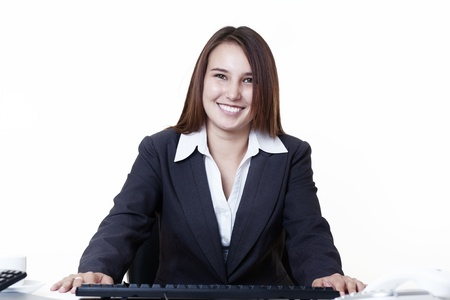 happy looking young looking business woman sitting at her desk Stock Photo - 14431673