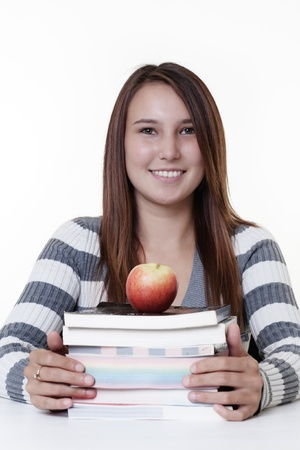snack time: young smiling woman working at her desk with a pile of books and a apple for snack time to keep her going