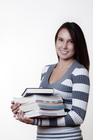 young smiling woman carrying books on white background  photo