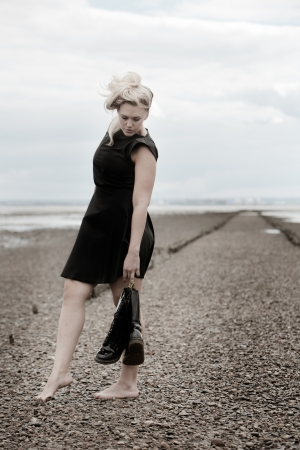 barefoot woman on a stoney beach wearing a dress and holding boots posing photo
