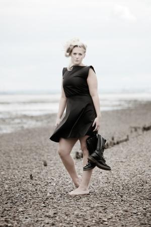 pieds nus femme: femme aux pieds nus sur une plage caillouteuse v�tue d'une robe et la tenue des bottes posant