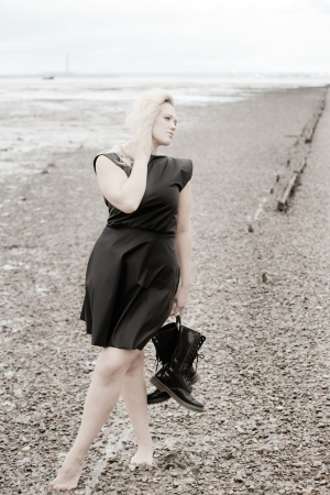 stoney: barefoot woman on a stoney beach wearing a dress and holding boots posing
