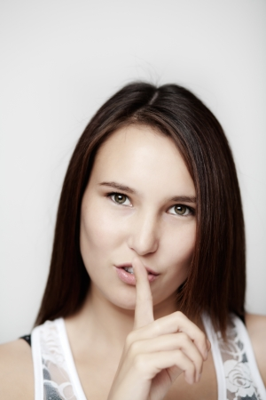 Woman making a keep it quiet sign with her finger shot on white background  Stock Photo - 14477721