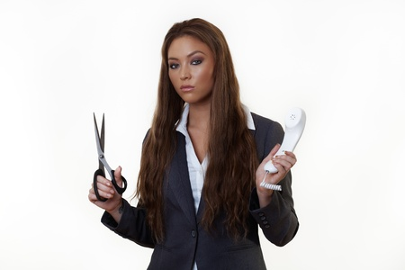 business woman with a pair of scissors cutting the cord to her work phone photo