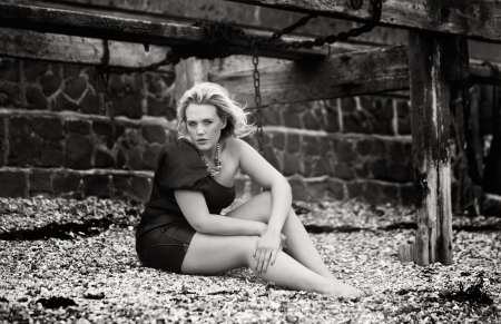 stoney: woman in a dress sitting on a stoney beach